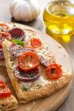 Stück Pizza mit Salami und Tomaten auf einem hölzernen Brett Stockbilder