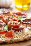 Stück Pizza mit Salami und Tomaten auf einem hölzernen Brett Lizenzfreie Stockfotografie