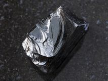 Stück roher Obsidian (vulkanisches Glas) auf Dunkelheit stockfoto
