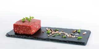 Stück rohes Rinderhackfleisch auf einem schwarzen Schieferbrett mit ganzem peppe Stockfotografie