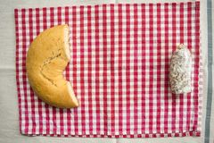 Stück Salami nahe einem wohlschmeckenden Donut Stockfotografie