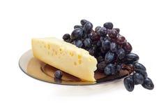 Stück Schweizer-artiger Käse und blaue Tafeltrauben Stockfotografie