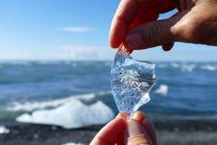 Stück tausendjähriges Eis das Sonnenlicht reflektierend gehalten von einer Person am Diamantstrand, Island stockbilder