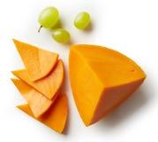 Stück und Scheiben des Cheddar-Käses Stockbild