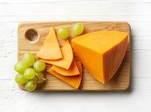 Stück und Scheiben des Cheddar-Käses Lizenzfreie Stockfotos