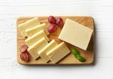 Stück und Scheiben des weißen Cheddar-Käses Lizenzfreie Stockfotografie