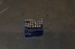 Stückchen mit Buchstaben und Zahlen auf Metalltabelle in der Werkstatt Lizenzfreie Stockfotos