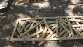 Stückchen rustikales Holz im langen Holzrahmen auf schmutziger Pflasterungs-Beschaffenheit mit Farbe - verlassener Garten-Garagen Lizenzfreies Stockfoto