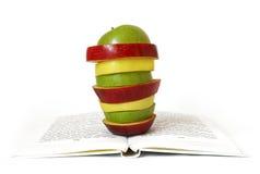 Stücke Äpfel auf dem Buch lizenzfreie stockbilder