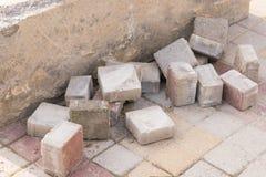 Stücke alte Pflastersteine liegen im Betonblock auf der Pflasterung Stockbild