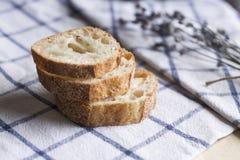 Stücke Brot- und Lavendelblumen auf der Tischdecke lizenzfreie stockfotografie