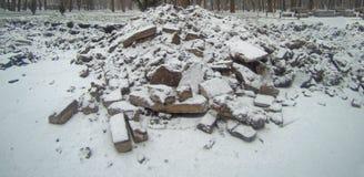 Stücke defekter Asphalt bedeckt mit Schnee oder Asche Stockfotografie