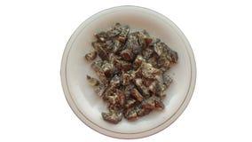 Stücke der getrockneten Wurst auf einer Platte lokalisiert auf weißem Hintergrund Stockbild