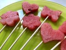 Stücke der Masse der Wassermelone werden mit einem Stempel geschnitten Sie werden verschiedene Formen gegeben Aufgereiht auf Aufs stockbilder
