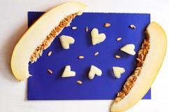 Stücke der Melone auf blauem Hintergrund bessert in Form eines Herzens und der Samen aus Stockfotos