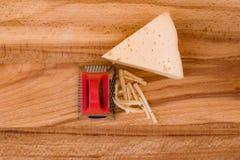 Stücke der Nahaufnahme des geriebenen Käses auf hölzernem Brett Lizenzfreies Stockfoto