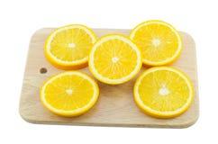 Stücke der Orange auf einem hölzernen Brett des Ausschnitts Stockfoto
