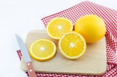 Stücke der Orange und des Messers auf einem hölzernen Brett des Ausschnitts Stockfotos