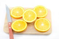 Stücke der Orange und des Messers auf einem hölzernen Brett des Ausschnitts Lizenzfreies Stockbild