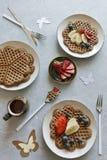 Stücke der selbst gemachten Waffel backen mit Banane und Blaubeeren auf den Platten auf grauem Hintergrund zusammen Stockfoto