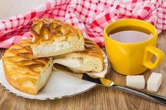 Stücke der Torte mit Hüttenkäse, Tasse Tee, Messer Lizenzfreie Stockfotos