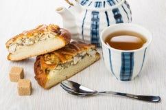 Stücke der Torte mit Huhn, Teekanne, Zucker, Tee, Teelöffel Lizenzfreie Stockfotos