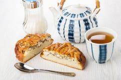 Stücke der Torte mit Huhn, Zucker, Teekanne, Tee in der Schale Stockbilder