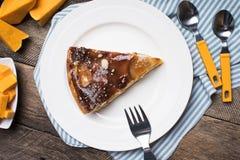 Stücke der Torte und des geschnittenen Kürbises auf Tabelle in der rustikalen Art Lizenzfreies Stockbild