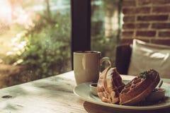 2 Stücke der Waffel mit einem weißen Tasse Kaffee auf dem Holztisch Lizenzfreie Stockfotografie
