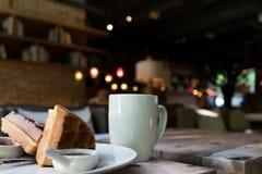 2 Stücke der Waffel mit einem weißen Tasse Kaffee auf dem Holztisch Lizenzfreies Stockfoto