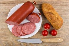 Stücke der Wurst in der Platte, im Brot, in den Tomaten und im Küchenmesser Stockfoto