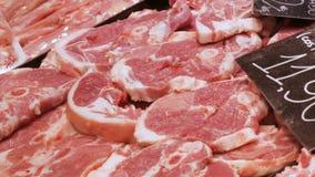 Stücke des frisch geschnittenen Rindfleisches oder des Schweinefleischmetzgers auf dem Fleischmarkt-Zählerabschluß oben stock footage