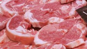 Stücke des frisch geschnittenen Rindfleisches oder des Schweinefleischmetzgers auf dem Fleischmarkt-Zählerabschluß oben stock video