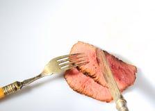 Stücke des gebratenen Steaks, des Weinlesemessers und der Gabel auf einem weißen Hintergrund Lizenzfreie Stockfotografie