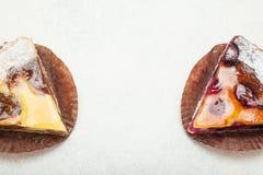 Stücke des Kuchens mit einer überlagerten Beerenschicht auf einem weißen Hintergrund stockbild
