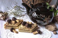 Stücke des Kuchens mit Schokoladenpilzen und -teekanne Stockbilder