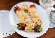 Stücke des Kuchens oder der Torte und der Erdbeeren auf Platte Stockbilder