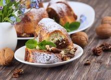 Stücke des Marmorkuchens besprüht mit Puderzucker und Blumen auf einem hölzernen Hintergrund stockfotografie