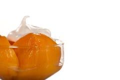 Stücke des Pfirsiches mit Sahne von Milch lizenzfreies stockbild