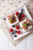 Stücke des Schokoladenkuchens mit Beerennahaufnahme auf einer Platte Verti Stockfotografie