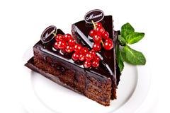 Stücke des Schokoladenkuchens mit Moosbeeren und Minze Lizenzfreie Stockfotos