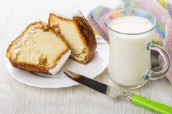 Stücke des Schwammkuchens mit Rum-gewürzt, Messer und Milch stockfotografie