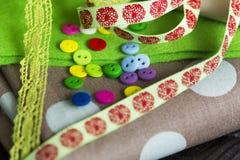 Stücke des Stoffes mit Tupfen, Grünfilz, grüner Spitze, Bändern und bunten Knöpfen Stockbilder