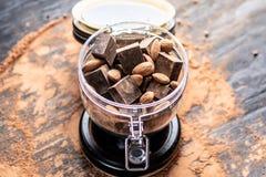 Stücke dunkle Bitterschokolade mit Kakao- und Nussmandeln auf hölzernem Hintergrund Konzept von Süßigkeitenbestandteilen lizenzfreie stockbilder