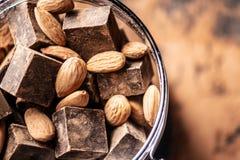 Stücke dunkle Bitterschokolade mit Kakao- und Nussmandeln auf hölzernem Hintergrund Konzept von Süßigkeitenbestandteilen stockfotografie