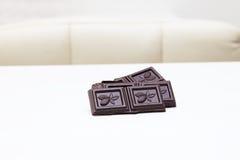 Stücke dunkle Schokolade auf einer weißen Tabelle Stockfotos