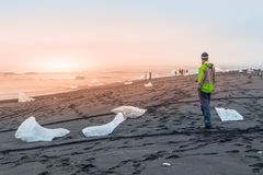 Stücke Eis auf schwarzem Sand, natürliches Detail, Island Mann, der auf dem schwarzen Strand steht Stockbilder
