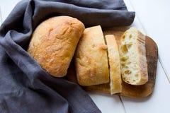 Stücke frisches knusperiges ciabatta Brot in einem grauen Stoff am hölzernen Schreibtisch Stockbilder
