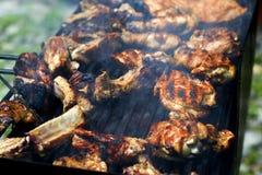 Stücke gebratenes Fleisch auf einem Gitter, mit Rauche und Feuer Gebratenes Fleisch auf Gitter mit Rauche lizenzfreie stockbilder