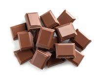 Stücke geschmackvolle Milchschokolade auf weißem Hintergrund stockfotografie